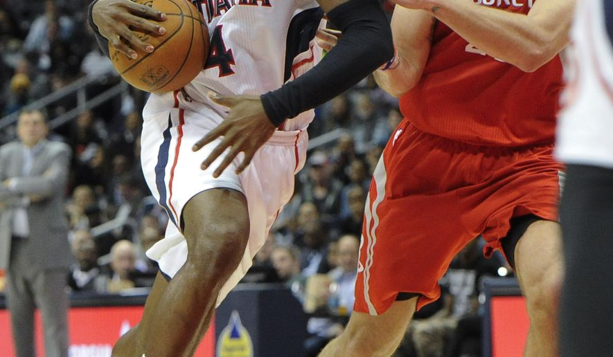 Atlanta Hawks forward forward Paul Millsap, left, drives through the lane past Houston Rockets Donatas Motiejunas, of Lithuania, during the first half of an NBA basketball game Tuesday, March 3, 2015, in Atlanta. (AP Photo/John Amis)