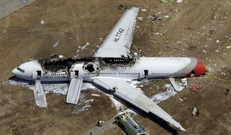In this July 6, 2013, aerial file photo, the wreckage of Asiana Flight 214 lies on the ground after it crashed at the San Francisco International Airport in San Francisco. On Tuesday, March 3, 2015, more than 70 passengers aboard an Asiana Airlines flight that crashed in San Francisco two years ago have reached a settlement in their lawsuits against the airline. (AP Photo/Marcio Jose Sanchez, File)