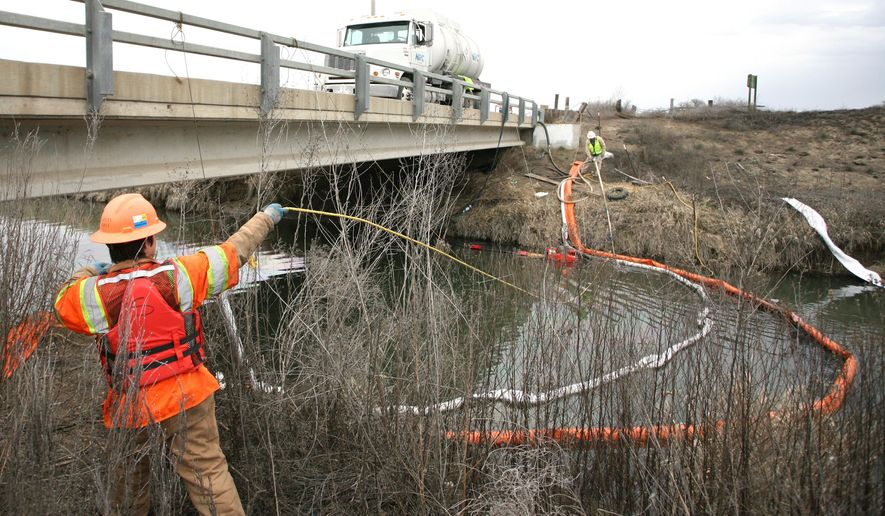 In this photo taken Monday, March 2, 2015, Stuart Weisenberger, a boom tender with environmental cleanup firm NRC, moves a vacuum tube upstream  in Sulphur Creek south of Sunnyside, Wash. Oil from a spill Sunday west of Sunnyside fouled the waters of the creek and the Yakima River as far as Prosser. (AP Photo/Yakima Herald-Republic, Ross Courtney)