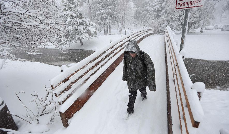 Shawn Sam trudges through the snow across the Rio de Flag in Wheeler Park, Monday, March 2, 2015, in Flagstaff, Ariz. Heavy snow forced the closure of schools, government offices in northern Arizona and the Grand Canyon's visitor centers Monday while rain fell in the state's desert terrain. (AP Photo/Arizona Daily Sun, Jake Bacon)