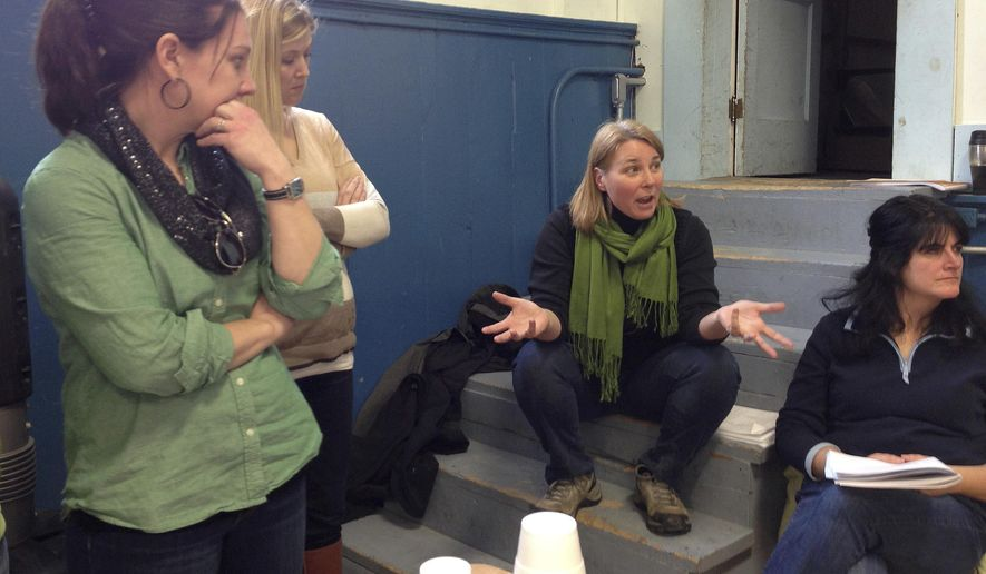 Tracy Puffer, center, asks questions at a town meeting about a proposal to open some town roads to ATV use during the state's town meeting day Tuesday, March 3, 2015, in Groton, Vt.  Voters rejected the proposal after a half an hour of discussion -- the longest debate since the town discussed a $1 fee for registering cats in 1999. (AP Photo/Lisa Rathke)
