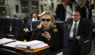 In this Oct. 18, 2011, photo, then-Secretary of State Hillary Rodham Clinton checks her Blackberry from a desk inside a C-17 military plane upon her departure from Malta, in the Mediterranean Sea, bound for Tripoli, Libya. Clinton used a personal email account during her time as secretary of state, rather than a government-issued email address, potentially hampering efforts to archive official government documents required by law. Clinton's office said nothing was illegal or improper about her use of the non-government account and that she believed her business emails to State Department and other .gov accounts would be archived in accordance with government rules. (Associated Press) **FILE**