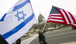 """A pro-Israel demonstrator waves flags, toward the U.S. Capitol in Washington, Tuesday, March 3, 2015, as Israeli Prime Minister Benjamin Netanyahu addressed a joint meeting of Congress. In a speech that stirred political intrigue in two countries, Netanyahu told Congress that negotiations underway between Iran and the U.S. would """"all but guarantee"""" that Tehran will get nuclear weapons, a step that the world must avoid at all costs. (AP Photo/Cliff Owen)"""