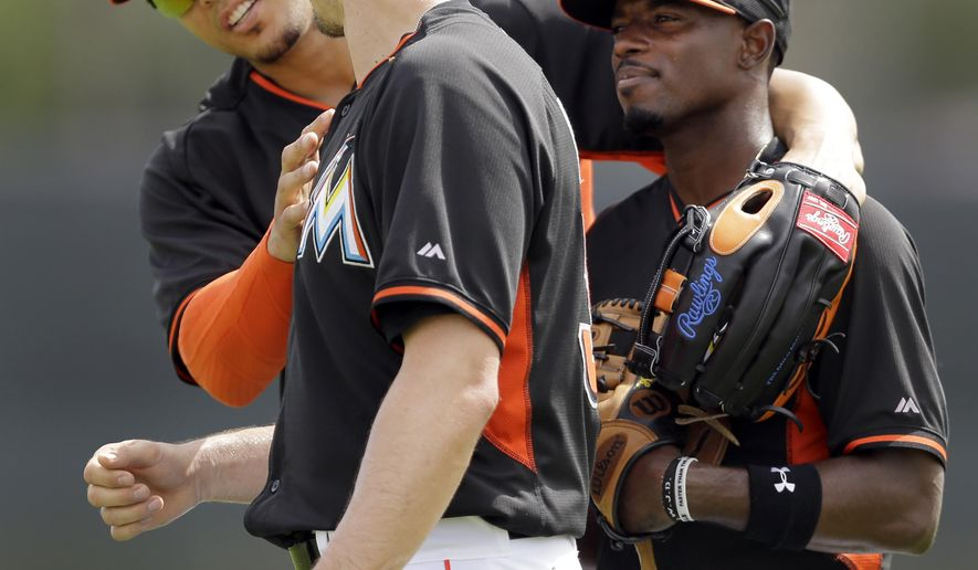 Miami Marlins' Giancarlo Stanton, left, puts his arm around Dee Gordon, right, while looking at the uniform of teammate Don Kelly during spring training baseball practice Sunday, March 1, 2015, in Jupiter, Fla. (AP Photo/Jeff Roberson)