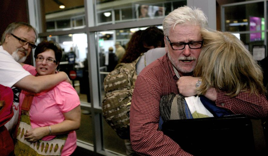 Freed aid workers Arlynn Hefta, right, and Kermit Paulson, left, embrace their wives at Hector International Airport, Tuesday, March 3, 2015 in Fargo, N.D. They were among four American missionaries who were released after several days of detention and questioning by Venezuelan authorities. (AP Photo/Bruce Crummy)