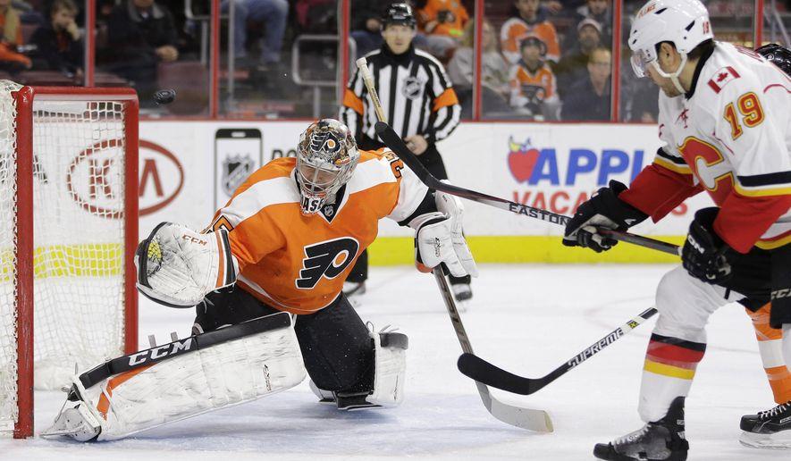 Philadelphia Flyers' Steve Mason, left, blocks a shot by Calgary Flames' David Jones during the first period of an NHL hockey game Tuesday, March 3, 2015, in Philadelphia. (AP Photo/Matt Slocum)