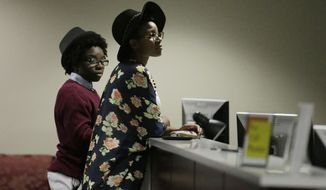 In this Feb. 9, 2015, file photo, Shanté Wolfe, left, and Tori Sisson, right, wait for their marriage license to be processed before becoming the first couple to file their marriage license in Montgomery, Ala. (AP Photo/Brynn Anderson, file)