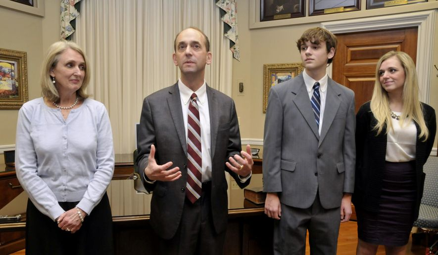 FILE - In this Jan. 12, 2015 photo, Tom Schweich, second from left, makes a few comments after his swearing-in ceremony with his wife, Kathy,  son Thomas Jr., and daughter Emile  in his Capitol office in Jefferson City. Schweich, who fatally shot himself in an apparent suicide on Feb. 26, 2015, had vowed to take down the state's most powerful politicians and donors, including his fellow Republicans, when he launched an anti-corruption campaign for governor last month. (AP Photo/News Tribune, Julie Smith, File)