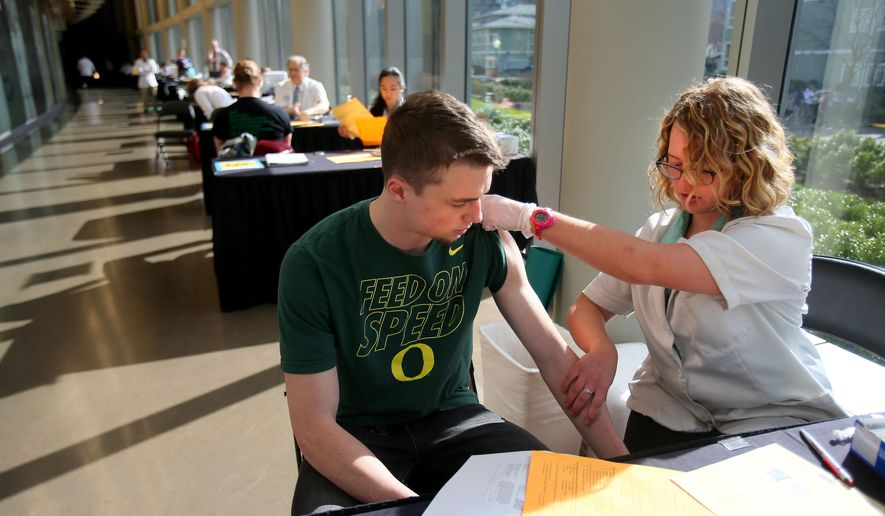 Pharmacist Jenna Wright administers the Meningitis B vaccine to University of Oregon freshman Drew Russert during a mass vaccination clinic at Matthew Knight Arena in Eugene, Ore. on Monday, March 2, 2015. The Meningitis B vaccine helps protect against the meningococcemia disease that has been diagnosed in four University of Oregon students, resulting in the death of one of those students. (AP Photo/The Register-Guard, Brian Davies)