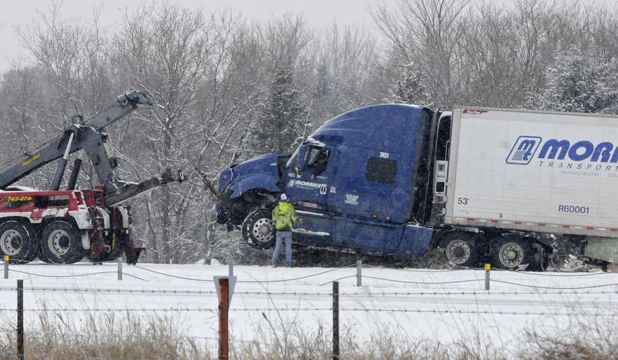 A tow truck lifts a semi truck on Interstate 94 west of Monticello, Minn., near the Hasty exit Tuesday March 3, 2015. Authorities closed the slippery stretch of Interstate 94 in central Minnesota due to numerous accidents. Snow turned the morning commute in the Twin Cities into a slippery mess as well, with numerous reports of crashes and spinouts. (AP Photo/The St. Cloud Times, Dave Schwarz)  NO SALES