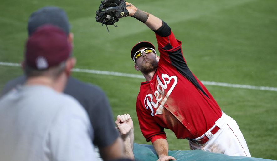Cincinnati Reds' Zack Cozart makes a catch during the second inning of a spring training exhibition baseball game against the Cleveland Indians, Tuesday, March 3, 2015, in Goodyear, Ariz. (AP Photo/John Locher)