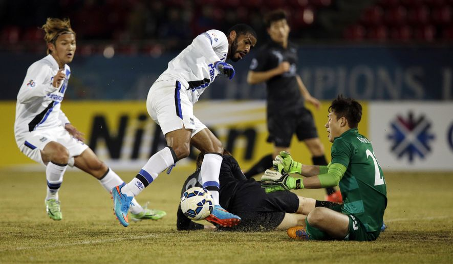 Anderson Patric Aguiar Oliveira, center, of Japan's Gamba Osaka in blocked by South Korea's Seongnam FC goalkeeper Park Jun-huk during their Group F soccer match in the Asian Champions League at Tancheon Sports Complex in Seongnam, South Korea, Tuesday, March 3, 2015. (AP Photo/Lee Jin-man)