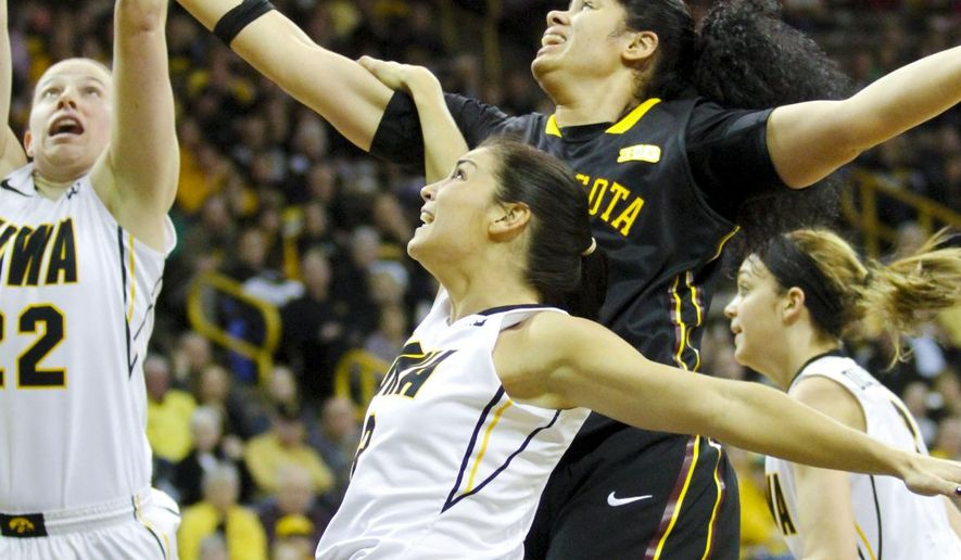 Minnesota center Amanda Zahui, center top, battles for a rebound with Iowa's Samantha Logic (22) and Claire Till (3) during the first half of an NCAA college basketball game, Sunday, March 1, 2015, in Iowa City, Iowa. (AP Photo/Matthew Holst)