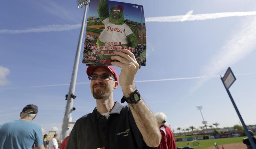Dirk Howard sells programs before a spring training baseball exhibition game between the Philadelphia Phillies and New York Yankees, Tuesday, March 3, 2015, in Clearwater, Fla. (AP Photo/Lynne Sladky)