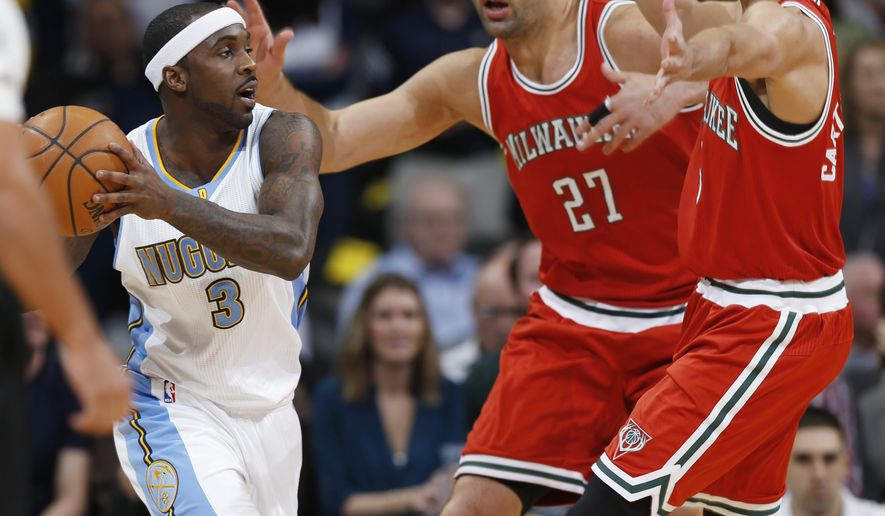 Denver Nuggets guard Ty Lawson, left, is trapped in the corner with the ball by Milwaukee Bucks center Zaza Pachulia and guard Michael Carter-Williams during the first quarter of an NBA basketball game Tuesday, March 3, 2015, in Denver. (AP Photo/David Zalubowski)