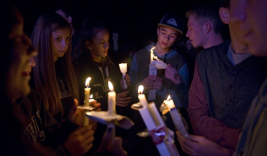 Cassidy Lin, Sidney Garcia, Alyssa Ashleigh, Payton Simpson, Jake Chaulk, Evan Shaughnessy, Davison Pease and Wesley Walters comfort each other and help light candles during a candlelight vigil for Jillian Jacobson in front of El Dorado High School on Monday, March 2, 2015 in Placentia, Calif.  Jacobson, a teacher, committed suicide by hanging herself in her classroom.  Students arriving at school found Jacobson's classroom door locked, Placentia police Lt. Eric Point said. Thinking she was late, they went next door to get another teacher, who returned with them and opened the door. Jacobson was found hanging from the ceiling. (AP Photo/The Orange County Register, Matt Masin)    MAGS OUT; LOS ANGELES TIMES OUT
