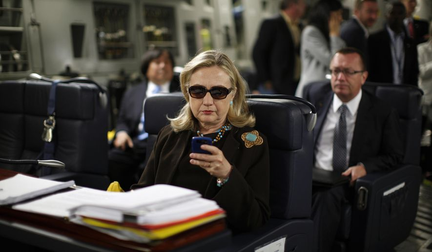 In this Oct. 18, 2011, file photo, then-Secretary of State Hillary Rodham Clinton checks her Blackberry from a desk inside a C-17 military plane upon her departure from Malta, in the Mediterranean Sea, bound for Tripoli, Libya. (AP Photo/Kevin Lamarque, Pool, File)