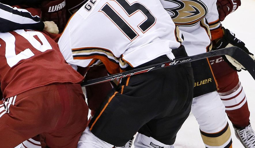 Anaheim Ducks' Ryan Getzlaf (15) and Arizona Coyotes' Shane Doan (19) start to fight during the second period of an NHL hockey game Tuesday, March 3, 2015, in Glendale, Ariz. (AP Photo/Ross D. Franklin)