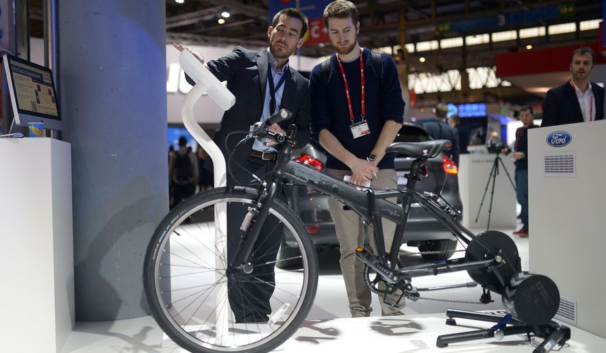 """A worker shows a visitor the e-bike from Ford at the Mobile World Congress, the world's largest mobile phone trade show in Barcelona, Spain, Wednesday, March 4, 2015. The bikes can be connected to a Bluetooth heart-rate monitor to optimize any workout, also programmed to let you cool down during the final stretch of your exercise session. """"We are in an experimental phase"""" said Eric Klampfl, Global Future Mobility Manager for Ford Research and Innovation Center. (AP Photo/Manu Fernandez)"""