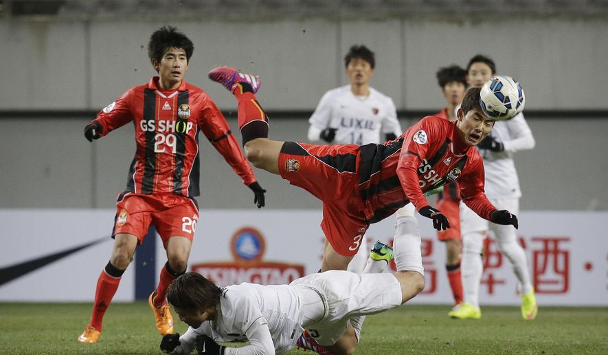 Lee Woong-hee, top right, of South Korea's FC Seoul fights for the ball against Hiroyuki Takasaki, bottom, of Japan's Kashima Antlers during their Group H soccer match in the Asian Champions League at Seoul World Cup Stadium in Seoul, South Korea, Wednesday, March 4, 2015. FC Seoul defeated Kashima Antlers with 1-0. (AP Photo/Ahn Young-joon)