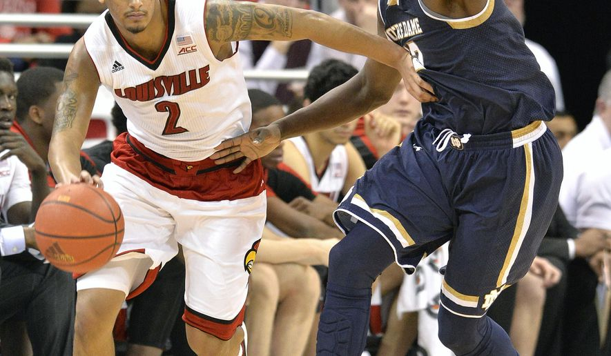 Louisville's Quentin Snider, left, attempts to drive around the defense of Notre Dame's Jerian Grant during the second half of an NCAA college basketball game Wednesday March 4, 2015, in Louisville, Ky. Notre Dame won 71-59. (AP Photo/Timothy D. Easley)