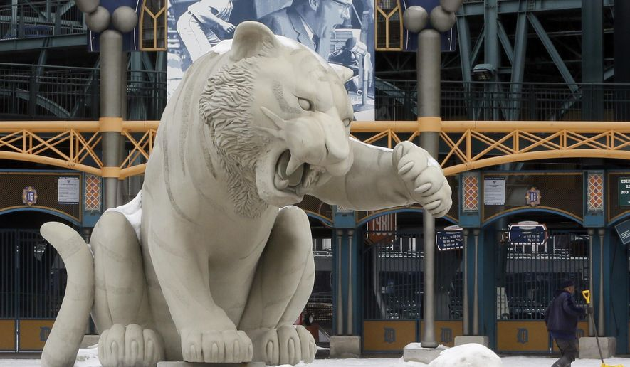 Snow is cleared from the sidewalk outside Comerica Park, home of the Detroit Tigers, Wednesday, March 4, 2015 in Detroit. The Tigers home opener is scheduled for April 6 against the Minnesota Twins. (AP Photo/Carlos Osorio)