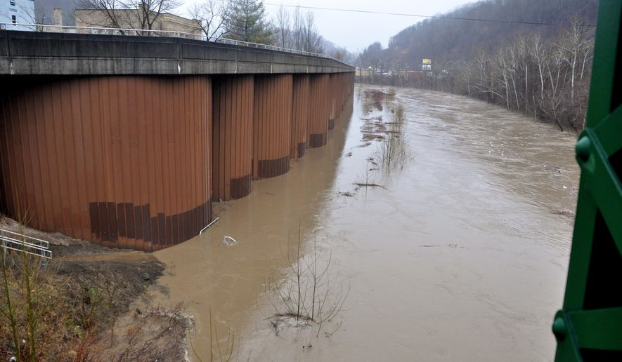 The Tug Fork River was rising in Williamson on Wednesday morning, March 4, 2015. Several smaller creeks and streams in Mingo and Logan County overflowed their banks.  Flood warnings have been issued as heavy rains move through West Virginia before giving way to significant snowfall. Schools in at least 15 counties sent students home early due to high water and other storm-related issues Wednesday. (AP Photo/Williamson Daily News, Kyle Lovern)
