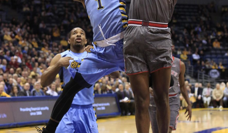 Marquette guard Duane Wilson, left, goes up for a shot against St. John's forward Chris Obekpa during the first half of an NCAA college basketball game Wednesday, March 4, 2015, in Milwaukee. (AP Photo/Darren Hauck)
