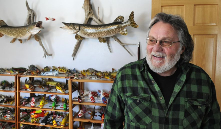 Dennis Bertram, 62, talks about the colors and sizes of then fish decoys he carves Tuesday, Feb. 24, 2015, in Belgrade, Minn. Bertram has been carving decoys for 35 years and spearing for 40, creating decoys from town inches long to almost 40 inches long. (AP Photo/St. Cloud Times, Jason Wachter) NO SALES