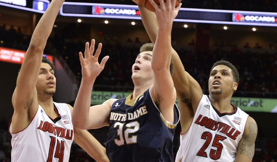 Notre Dame's Steve Vasturia (32) shoots between the defense of Louisville's Anas Mahmoud, left, and Wayne Blackshear during the first half of an NCAA college basketball game Wednesday, March 4, 2015, in Louisville, Ky. (AP Photo/Timothy D. Easley)