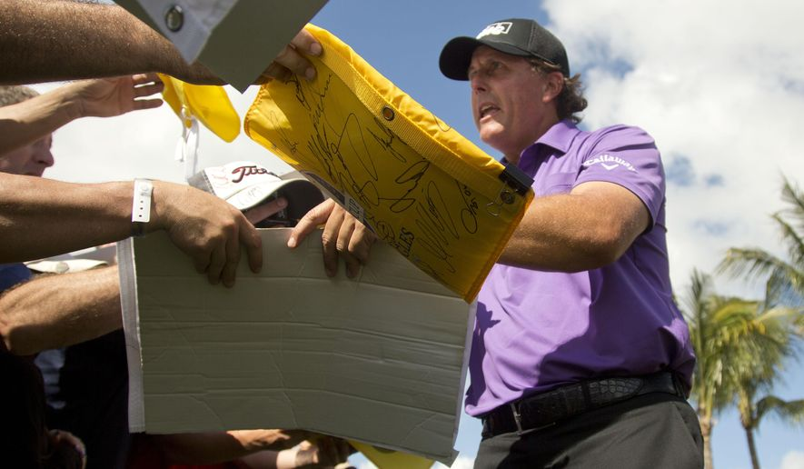 Phil Mickelson signs autographs after a practice round for the Cadillac Championship golf tournament in Doral, Fla., Wednesday, March 4, 2015. (AP/J Pat Carter)
