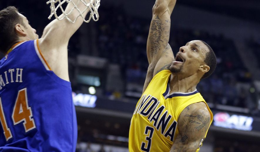 Indiana Pacers guard George Hill (3) attempts a dunk over New York Knicks forward Jason Smith (14) during the second half of an NBA basketball game Wednesday, March 4, 2015, in Indianapolis. (AP Photo/Michael Conroy)