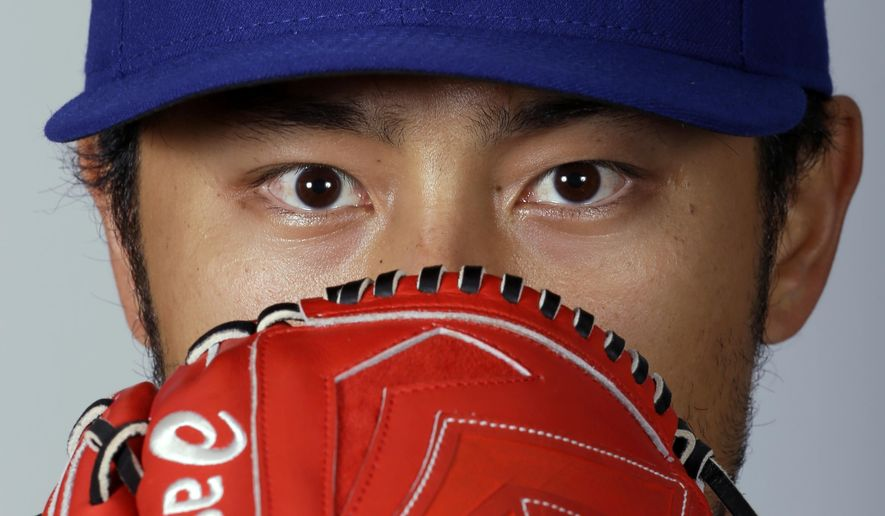 Texas Rangers' Yu Darvish poses with his glove on photo day during baseball spring training, Monday, March 2, 2015, in Surprise, Ariz. (AP Photo/Charlie Riedel)