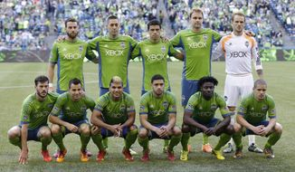 FILE - In this May 7, 2014, file photo, Seattle Sounders players, including defender Zach Scott, upper left, and forward Clint Dempsey, second from upper left, pose for the traditional team portrait before an MLS soccer match against FC Dallas in Seattle. As the MLS grows, there remains a significant economic gap among player salaries. Scott, who has started 67 MLS regular season games in his six seasons, has never made more than $52,500 per season, but Dempsey, who is also captain of the U.S. men's national team, made more than $6 million in guaranteed compensation in the 2014 season. (AP Photo/Ted S. Warren, file)