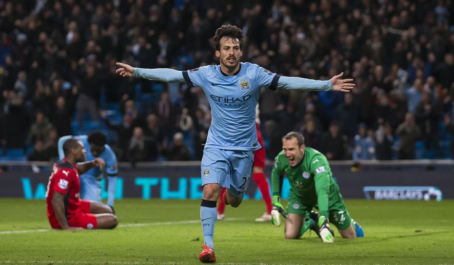 Manchester City's David Silva, centre, celebrates after  scoring past Leicester's goalkeeper Mark Schwarzer, right,  during the English Premier League soccer match between Manchester City and Leicester City at the Etihad Stadium, Manchester, England, Wednesday March 4, 2015. (AP Photo/Jon Super)
