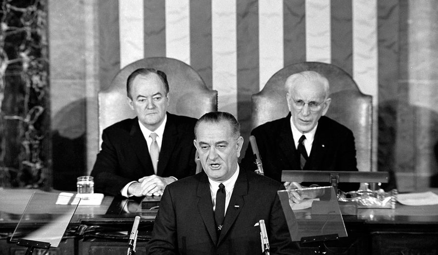 FILE - In this March 15, 1965 file photo, U.S. President Lyndon B. Johnson addresses a joint session of Congress in Washington where he urged the passing of the Voting Rights Act and spoke of his experience as a young teacher in a segregated, Mexican-American school. Vice President Hubert Humphrey is at left and House Speaker John McCormack is at right. (AP Photo/File)