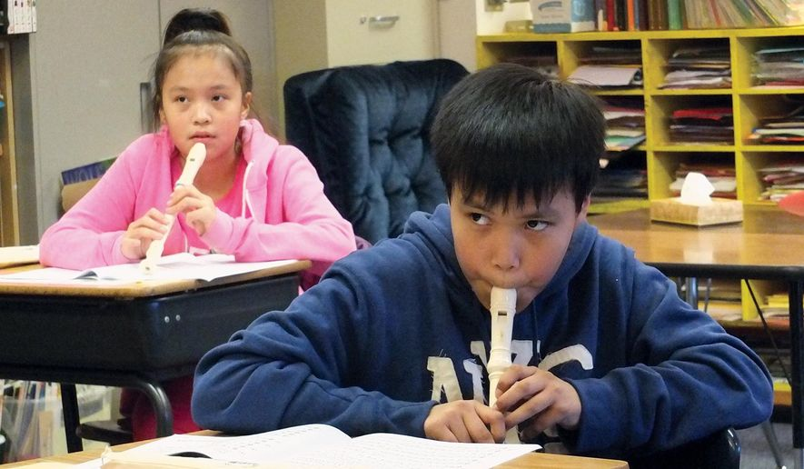 In a Feb. 4, 2015 photo, Garrison Willis, foreground, practices on the recorder as Salvation Army Major Cathy Quinn, not seen, teaches music in their Angoon School class, in Angoon, Alaska.  It's been a while since kids in Angoon have had regular music classes, but Salvation Army Major Cathy Quinn is volunteering in the schools to try and fix that. She got a donation of 10 recorders - an accessible flute-like instrument on which to first teach children how to read and play music - and knew she could find a use for them in the classroom.(AP Photo/Capital City Weekly, Mary Catharine Martin)