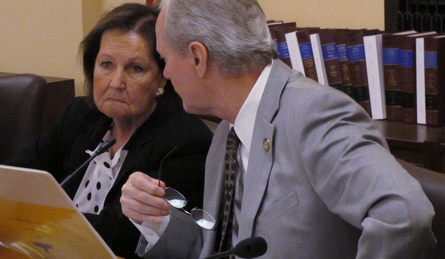 CORRECTS DATE Kansas state Reps. Sharon Schwartz, left, a Washington Republican, and Gene Suellentrop, right, a Wichita Republican, confer during a House Appropriations Committee meeting, Wednesday, March 4, 2015, at the Statehouse in Topeka, Kan. The committee is proposing to launch a hunt for budget efficiencies. (AP Photo/John Hanna)