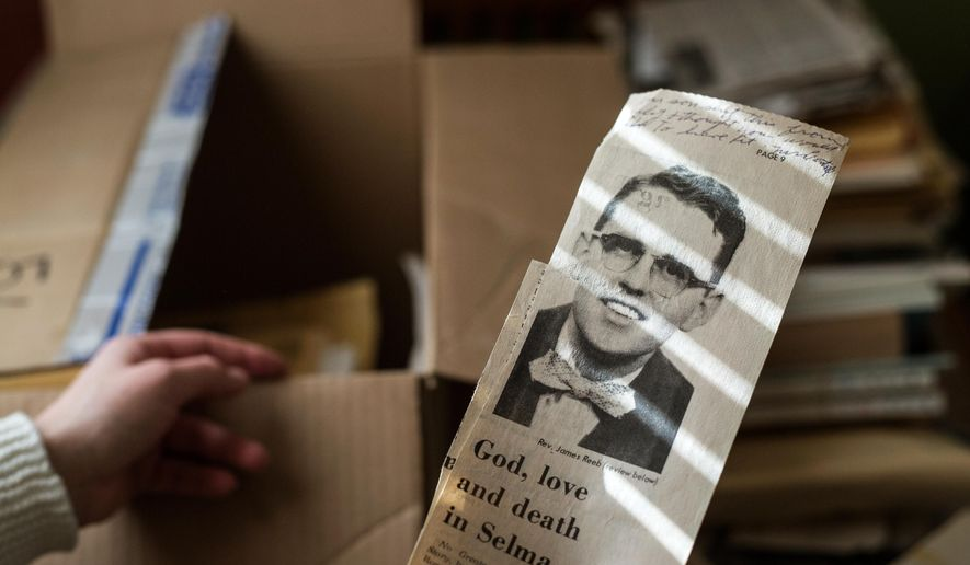 In this photo taken on Friday, Jan. 9, 2015, a news clipping paying homage to Rev. James Reeb is held by his granddaughter Leah in Casper, Wyo.  Reeb died March 11, 1965, in Birmingham, Ala., after traveling to Selma, Ala., and being attacked for his involvement in the fight for civil rights. (AP Photo/The Casper Star-Tribune, Ryan Dorgan)