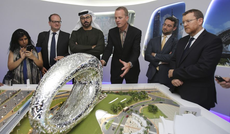 """Emirati Minister of Cabinet Affairs Mohammed al-Gergawi, 3rd left, listens to architect Shaun Killa, center, who won the competition for the design. as he describes the concept of the """"Museum of the Future"""" in front of the project's model at the UAE Prime Minister Office in Dubai, United Arab Emirates, Wednesday, March 4, 2015. Al-Gergawi told reporters Wednesday the museum in Dubai will showcase innovations in design and technology, in fields such as transportation, health and education. (AP Photo/Kamran Jebreili)"""