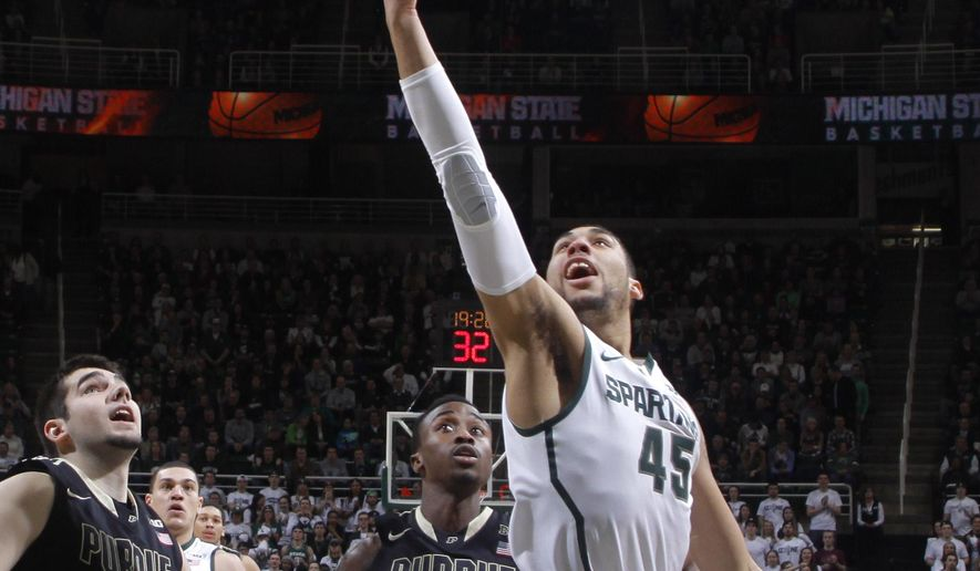 Michigan State's Denzel Valentine (45) puts up a shot against Purdue's Dakota Mathias (31) and Jon Octeus (0) during the first half of an NCAA college basketball game Wednesday, March 4, 2015, in East Lansing, Mich. (AP Photo/Al Goldis)