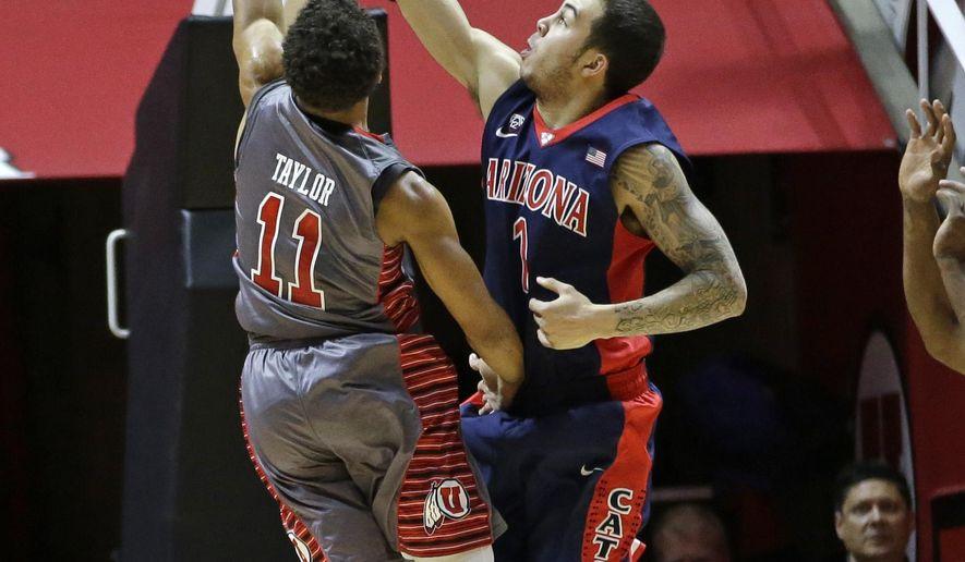 Utah guard Brandon Taylor (11) shoots as Arizona guard Gabe York (1) defends in the first half of an NCAA college basketball game Saturday, Feb. 28, 2015, in Salt Lake City. (AP Photo/Rick Bowmer)