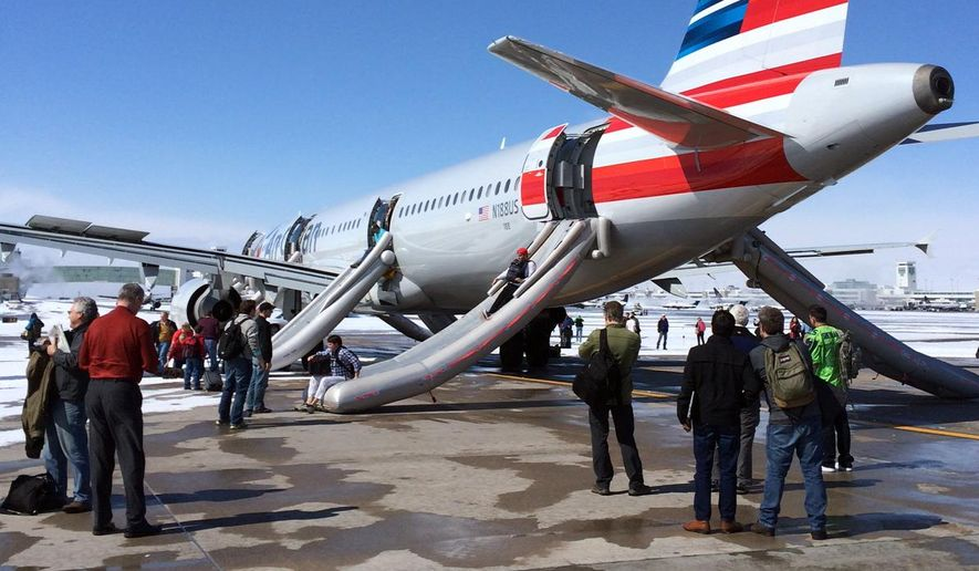 In this photo provided by Andy Long passengers slide down emergency chutes after an American Airlines flight from Charlotte, N.C., soon after landing in Denver, Wednesday, March 4, 2015. The plane, operated by U.S. Airways, was taxiing to the gate at Denver International Airport when smoke was reported in the aircraft just before noon, airport spokeswoman Mindy Crane said. The captain ordered that the chutes be activated, and the passengers and crew members slid down to safety from Flight 445 before being taken by bus to the concourse, said Crane and American Airlines spokeswoman Andrea Huguely. (AP Photo/Andy Long)
