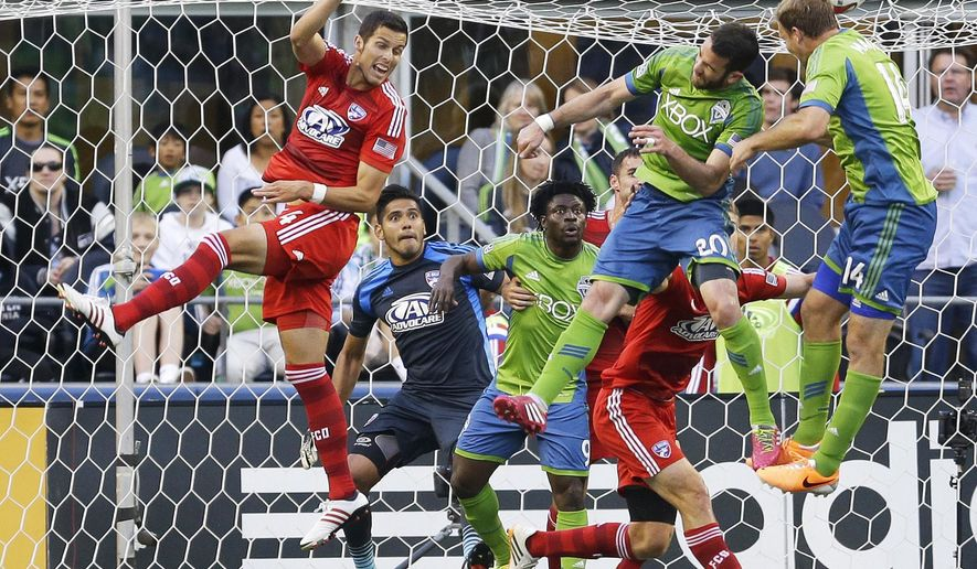 FILE -  In this May 7, 2014, file photo, FC Dallas goalkeeper Raul Fernandez, second from left, and Dallas' Matt Hedges, left, watch as Seattle Sounders' Zach Scott (20) and Chad Marshall, right, go for a header as Sounders' Obafemi Martins, third from left, looks on during an MLS soccer match in Seattle. As the MLS grows, there remains a significant economic gap among player salaries. Scott, who has started 67 MLS regular season games in his six seasons, has never made more than $52,500 per season. (AP Photo/Ted S. Warren)