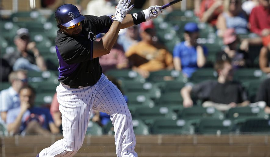 Colorado Rockies' Wilin Rosario hits a single during the second inning of a spring training baseball game against the Arizona Diamondbacks, Wednesday, March 4, 2015, in Scottsdale, Ariz. (AP Photo/Darron Cummings)