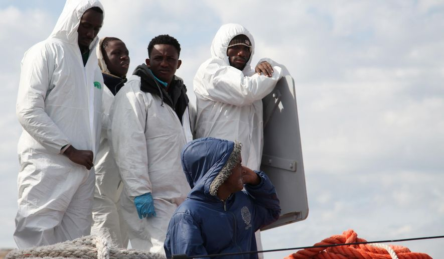 Rescued migrants wait to disembark from an Italian Coast Guard vessel in Porto Empedocle, Sicily, southern Italy, Wednesday, March 4, 2015. In a dramatic sea rescue north of Libya, a flotilla of rescue ships saved nearly 1,000 migrants and refugees, while 10 migrants perished in the southern Mediterranean, Italian officials said Wednesday. The rescue vessels, including from Italy's coast guard and navy, and three cargo ships, saved 941 people in seven separate operations that began Tuesday, Italy's coast guard said. The survivors were being ferried to southern Italian ports. The migrants had been aboard five motorized dinghies and two larger vessels. One of the larger boats capsized, and 10 bodies were spotted or plucked from the sea. According to Interior Ministry figures, 7,882 migrants arrived on Italian coasts in the first two months of this year, compared to 5,506 in that period in 2014. The coast guard said the migrants saved in the latest rescues claimed to be Syrians, Palestinians, Libyans, Tunisians or from sub-Saharan Africa. (AP Photo/Francesco Malavolta)