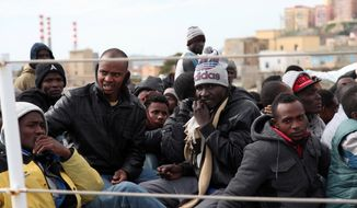 Migrants wait to disembark from an Italian Coast Guard vessel after being rescued in Porto Empedocle, Sicily, southern Italy, Wednesday, March 4, 2015.  In a dramatic sea rescue north of Libya, a flotilla of rescue ships saved nearly 1,000 migrants and refugees, while 10 migrants perished in the southern Mediterranean, Italian officials said Wednesday. The rescue vessels, including from Italy's coast guard and navy, and three cargo ships, saved 941 people in seven separate operations that began Tuesday, Italy's coast guard said. The survivors were being ferried to southern Italian ports. The migrants had been aboard five motorized dinghies and two larger vessels. One of the larger boats capsized, and 10 bodies were spotted or plucked from the sea. According to Interior Ministry figures, 7,882 migrants arrived on Italian coasts in the first two months of this year, compared to 5,506 in that period in 2014. The coast guard said the migrants saved in the latest rescues claimed to be Syrians, Palestinians, Libyans, Tunisians or from sub-Saharan Africa. (AP Photo/Francesco Malavolta)