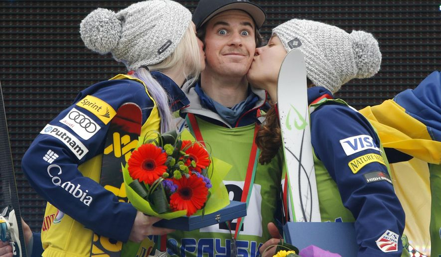 Mac Bohonnon, center, is kissed by Ashley Caldwell, right, and Kiley McKinnon, left, all of the U.S, as they stand on a podium celebrating their victory in the FIS Freestyle Ski World Cup 2015 event in Raubichi, on the outskirts of Minsk, Belarus, Sunday, March 1, 2015. Ashley Caldwell took gold, Mac Bohonnon and Kiley McKinnon took silver. (AP Photo/Sergei Grits)