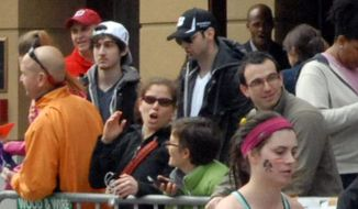 This Monday, April 15, 2013, file photo provided by Bob Leonard shows Dzhokhar Tsarnaev, second from left, and Tamerlan Tsarnaev, center, standing in the crowd as Boston Marathon runners headed to the finish line on Boylston Street in Boston. Tamerlan Tsarnaev died during a police pursuit of the duo four days after the marathon. (AP Photo/Bob Leonard, File)