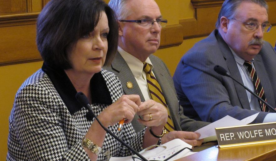 Kansas state Rep. Kathy Wolfe Moore, left, a Kansas City Democrat, asks questions during a House Taxation Committee hearing on Republican Gov. Sam Brownback's income tax proposals, Wednesday, March 4, 2015, at the Statehouse in Topeka, Kan. Watching to her right are Republican Reps. Don Hineman of Dighton and John Edmonds of Great Bend. (AP Photo/John Hanna)